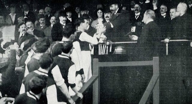 King George V presents the FA Cup to the victorious Burnley team in 1914. It was the first time the monarch had attended the final and the last final to be played in Crystal Palace park.