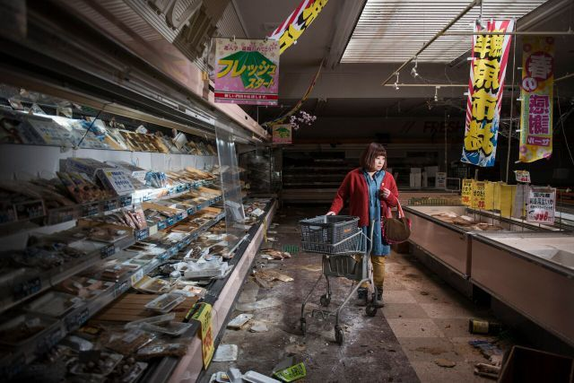 A woman is staged to appear as if she's shopping in an abandoned supermarket in the Fukushima no go zone. Copyright Carlos Ayesta and Guillaume Bression