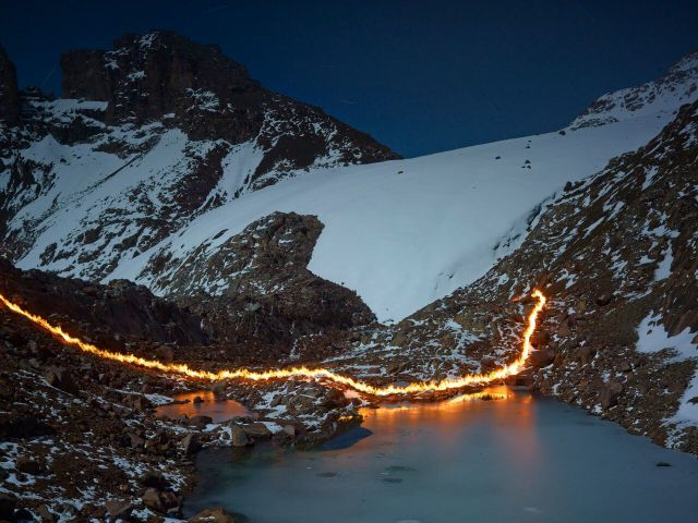 The line of flames marks where the glacier extended to in 1987. It has receded 120 metres since. Copyright Simon Norfolk.