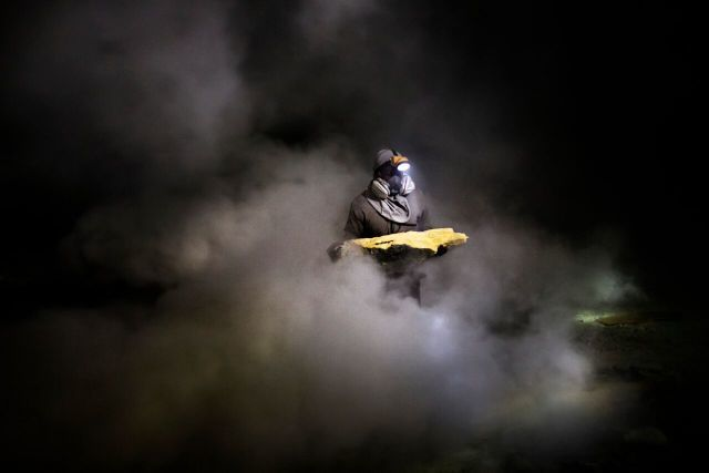 A miner recovers sulphur, known locally as Devil's Gold, from inside a volcano. Copyright Luca Catalano Gonzaga