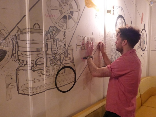 Artist Patrick Vale puts some finishing touches to a wraparound mural of cinematic history in the cafe.