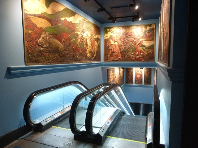 Above the escalators, Grade II listed friezes by Gerald Moira, saved from the building's early days as Scott's restaurant. They depict Arthurian themes.