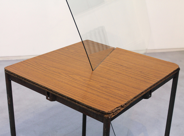 In this surreal work, a pane of glass slices into a table.