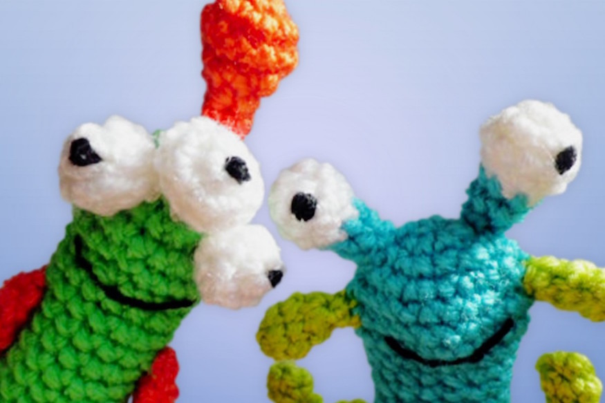 Two smiling crocheted aliens