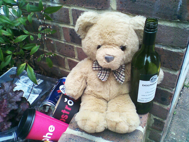 Teddy bear on the floor clutching a bottle of wine.