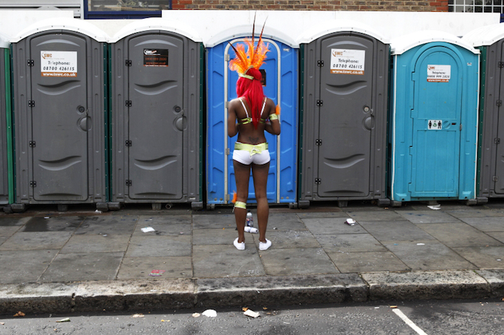 Man in feather headress queues for portaloo toilets at Notting Hill Carnival