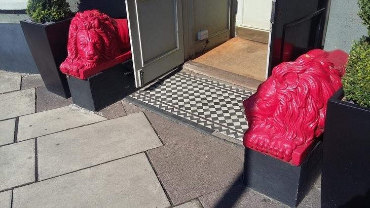 Two red lions beside a door.