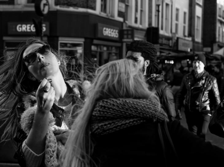 Woman applies lipstick, Portobello Road