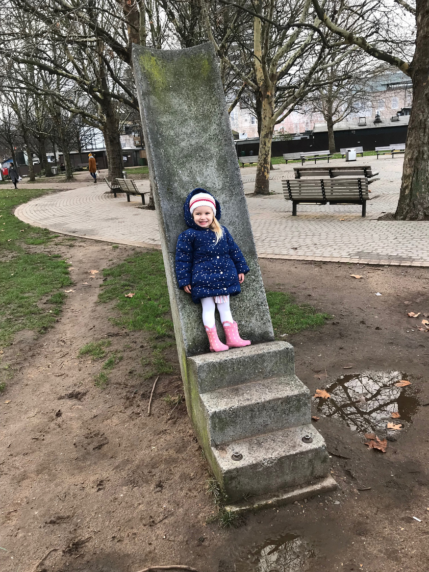 Sloped bench thing with a small child who likes jumping up and down in muddy puddles