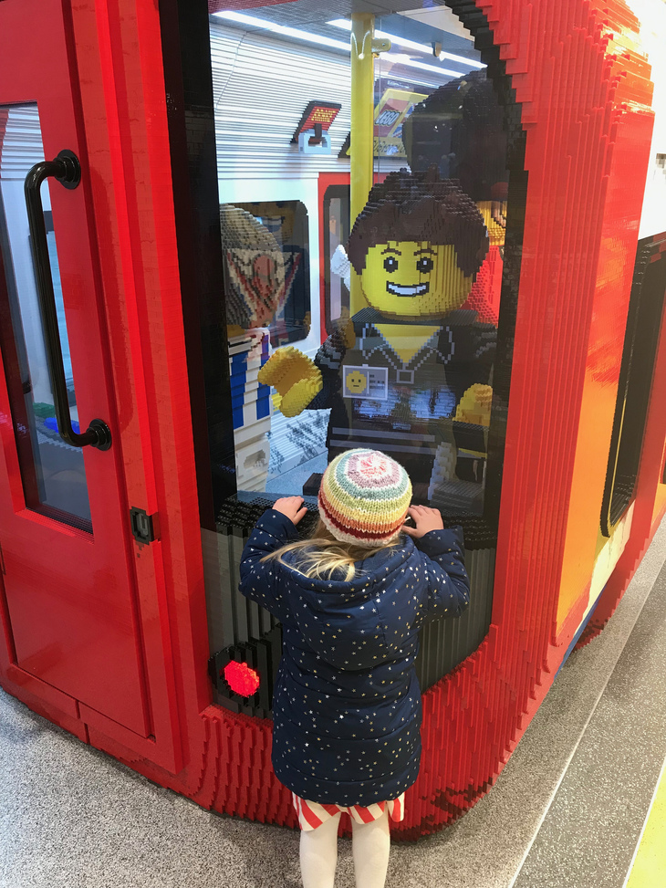 A child stares into the cab of a tube train, unaware of the peril she is in. But it is OK, for this is a lego tube train and not a real tube train, which would, of course, be fatal.