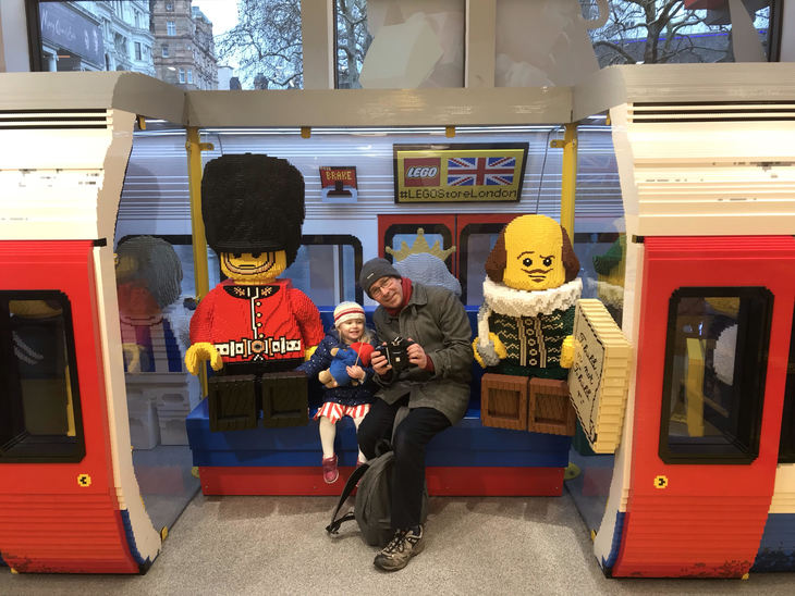 Man and delighted nipper on a lego tube train. They are sat between a soldier and William Shakespeare, which is a temporal impossibility.