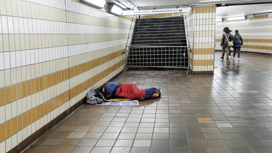 A homeless person sleeping in Charing Cross station