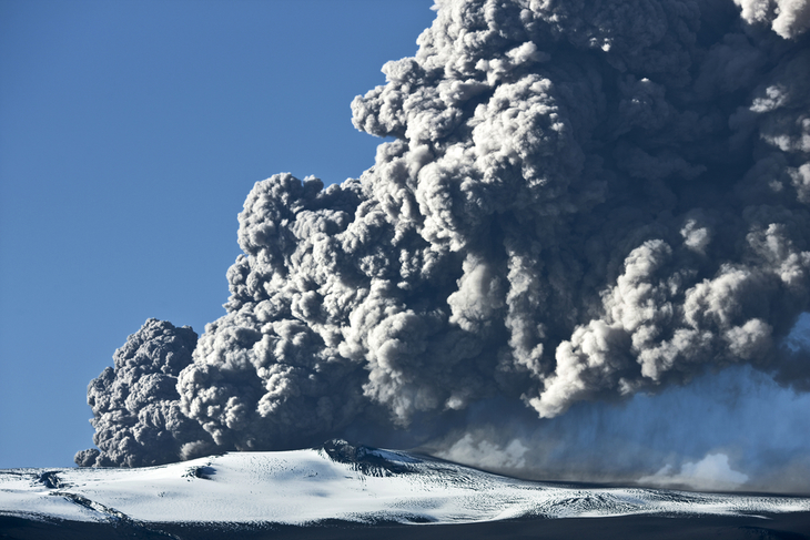 A volcano erupting a cloud of ash