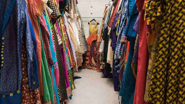 Colourful costumes hanging in two rows in a wardrobe storage area at National Theatre