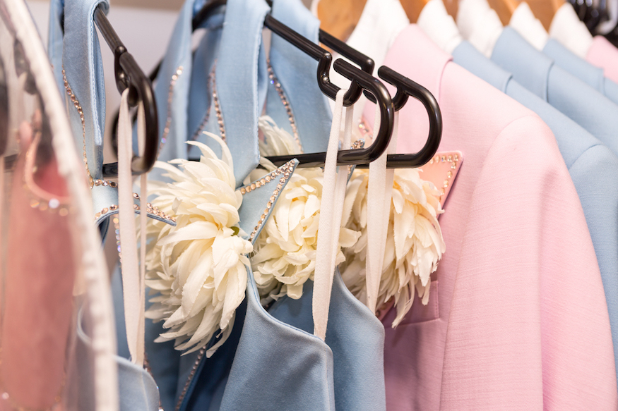 Pale pink and pale blue costumes hanging on a clothes rail at National Theatre