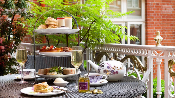 Afternoon tea served on a three tiered stand in the garden of St Ermin's Hotel near Westminster