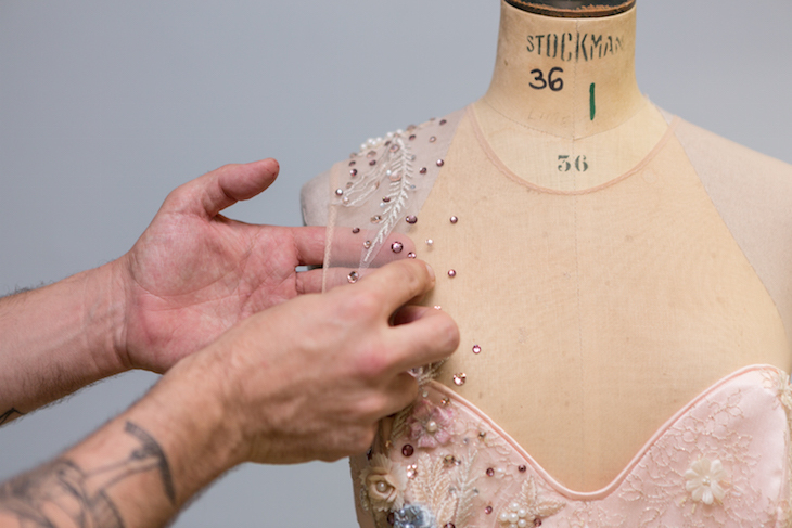 Close-up shot of a hand sewing sequins onto the shoulder of a pink dress on a mannequin, in National Theatre's wardrobe department