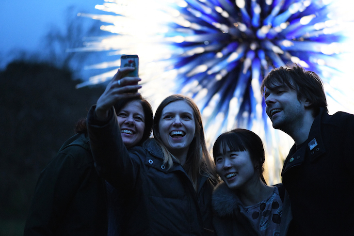 Four people taking a selfie in front of Sapphire Star by Dale Chihuly glass sculpture at Chihuly Nights at Kew Gardens