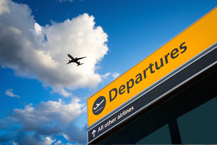 Aeroplane in the sky above a departures sign at Heathrow Airport
