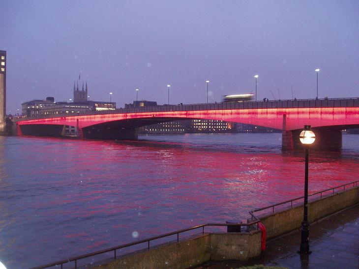 London Bridge illuminated in red in the rain
