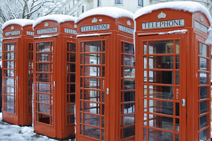 Four London red telephone boxes with snow on top
