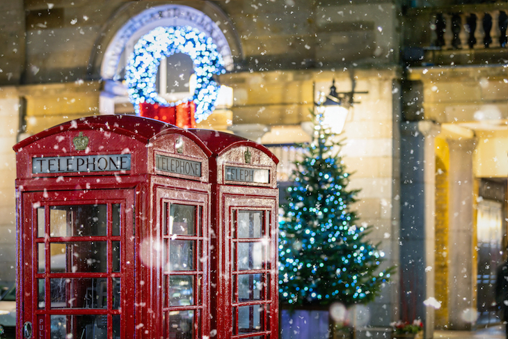 Christmas decorations and a red phone box in Covent Garden, London, with snow falling