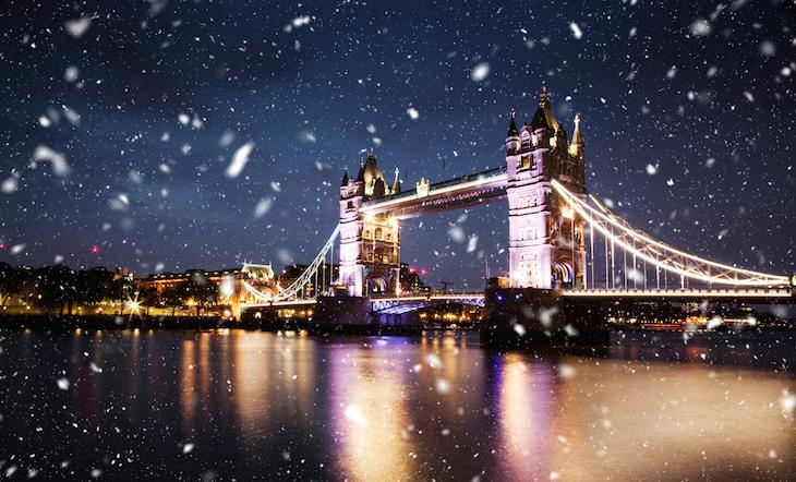 Snow falling at Tower Bridge, London, at night