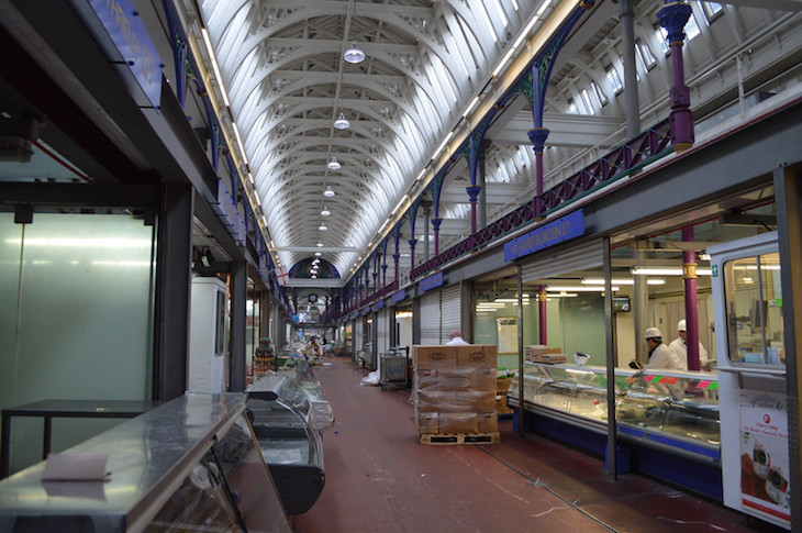 Deserted corridor of Smithfield Meat Market, with closed meat shops on either side. Soon to be home to the new Museum of London.