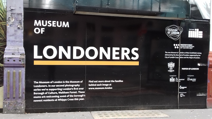 Hoardings outside new Museum of London building in Smithfield, saying 'Museum of Londoners' and giving details about the building's renovation.