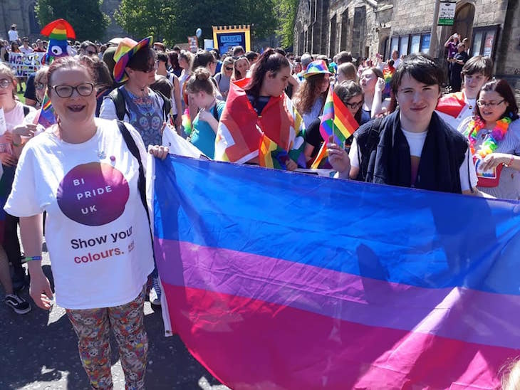 People march with the Bi flag at Bi Pride