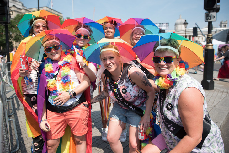 A group of 7 people wearing rainbow umbrella hats at Pride in London