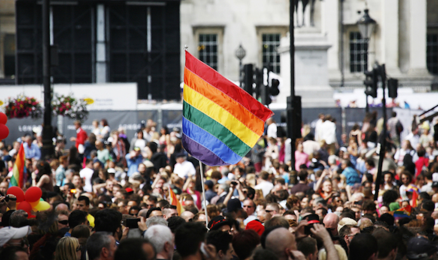 A rainbow flag waves in a crowd at Pride in London