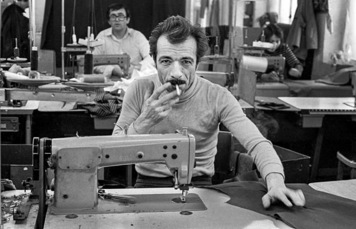 Man smoking at sewing machine