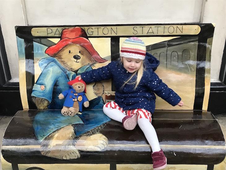 Girl and bear on the Paddington bench