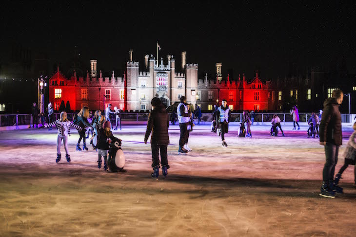 People ice skating on a rink in front of Hampton Court Palace at night. The palace front is illuminated in red.