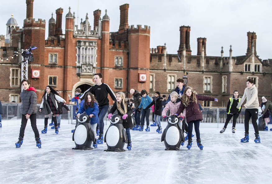 People ice skating in front of Hampton Court Palace, London, in daylight.