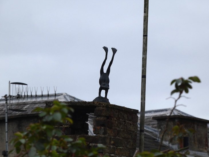 An upside down statue of a frog doing a handstand, on top of a garden wall, on Frog Lane in Tunbridge Wells, Kent