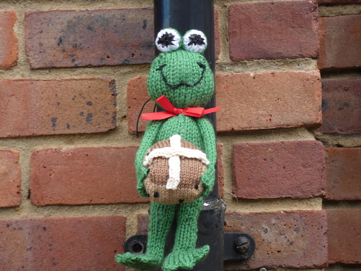 A knitted green frog cuddly toy holding a knitted hot cross bun, attached to a drain pipe on a brick wall on Frog Lane in Tunbridge Wells, Kent