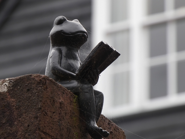 A small statue of a black frog, sitting on a wall and reading  a book, on Frog Lane in Tunbridge Wells, Kent