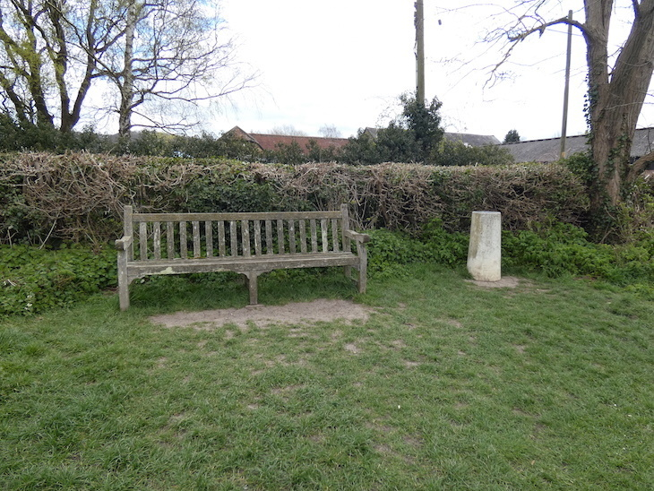 A bench in a grassy field, in front of a hedge, with a concrete pillar to its right, part of the Otford Solar System Walking Route