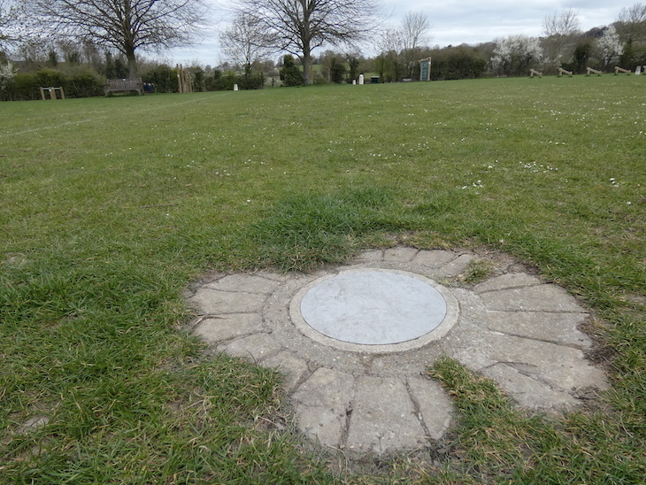 A silver metal plaque representing Mars, surrounded by bricks, sunk into a grassy field, part of the Otford Solar System Walking Route