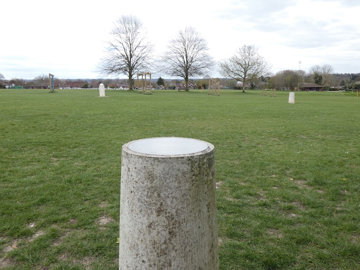 A concrete pillar representing Venus in the foreground, with two other pillars in the background, in a grassy field, part of the Otford Solar System Walking Route