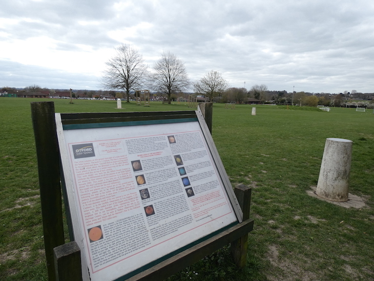 An information board giving information about the Otford Solar System, with a concrete pillar representing Venus next to it, in a grassy field.