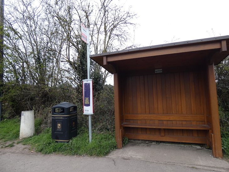 A wooden bus shelter, a bus stop pole, a litter bin and a concrete pillar (representing Uranus), lined up on the grass verge at the side of a road.