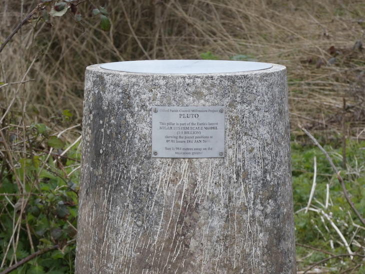 A concrete pillar in a field, with a metal plaque identifying it as part of the Otford Solar System Walking Route