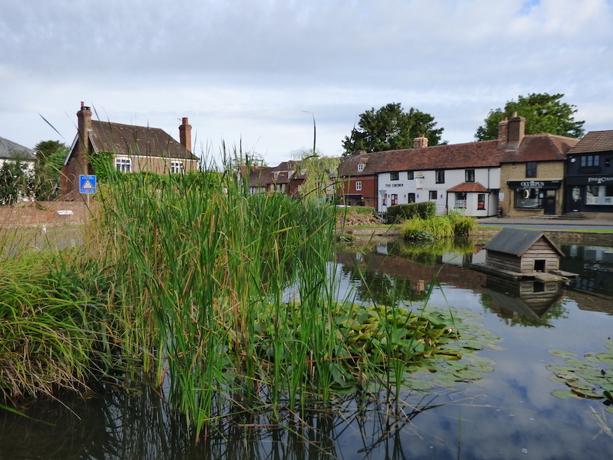 A duck pond with duck house sits in the middle of a roundabout, with shops in the background, in the village of Otford in Kent.