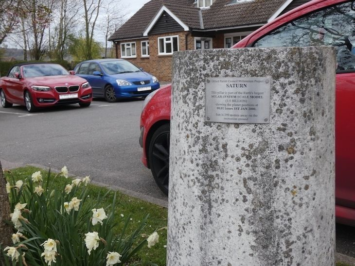 A doctors surgery car park, with a concrete pillar embedded in a grass verge, with a metal plaque detailing it as part of the Otford Solar System