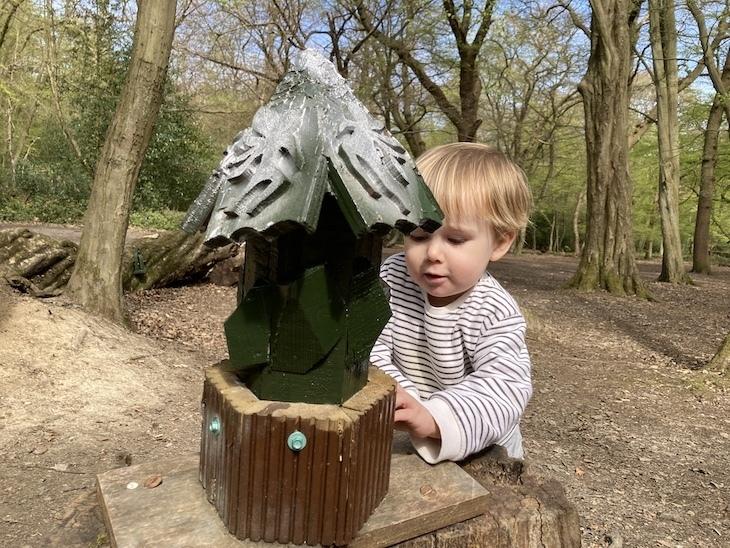 Little boy inspecting a fairy chalet