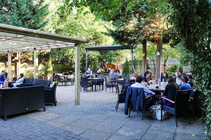 Queen's Head, Brook Green beer garden with assorted people at tables.