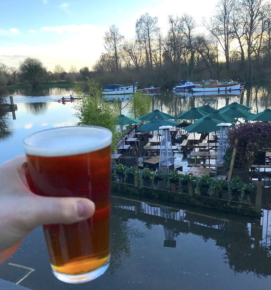 White Swan Twickenham beer garden under high-tide flood. A cocky drinker up on a balcony salutes its inundation.